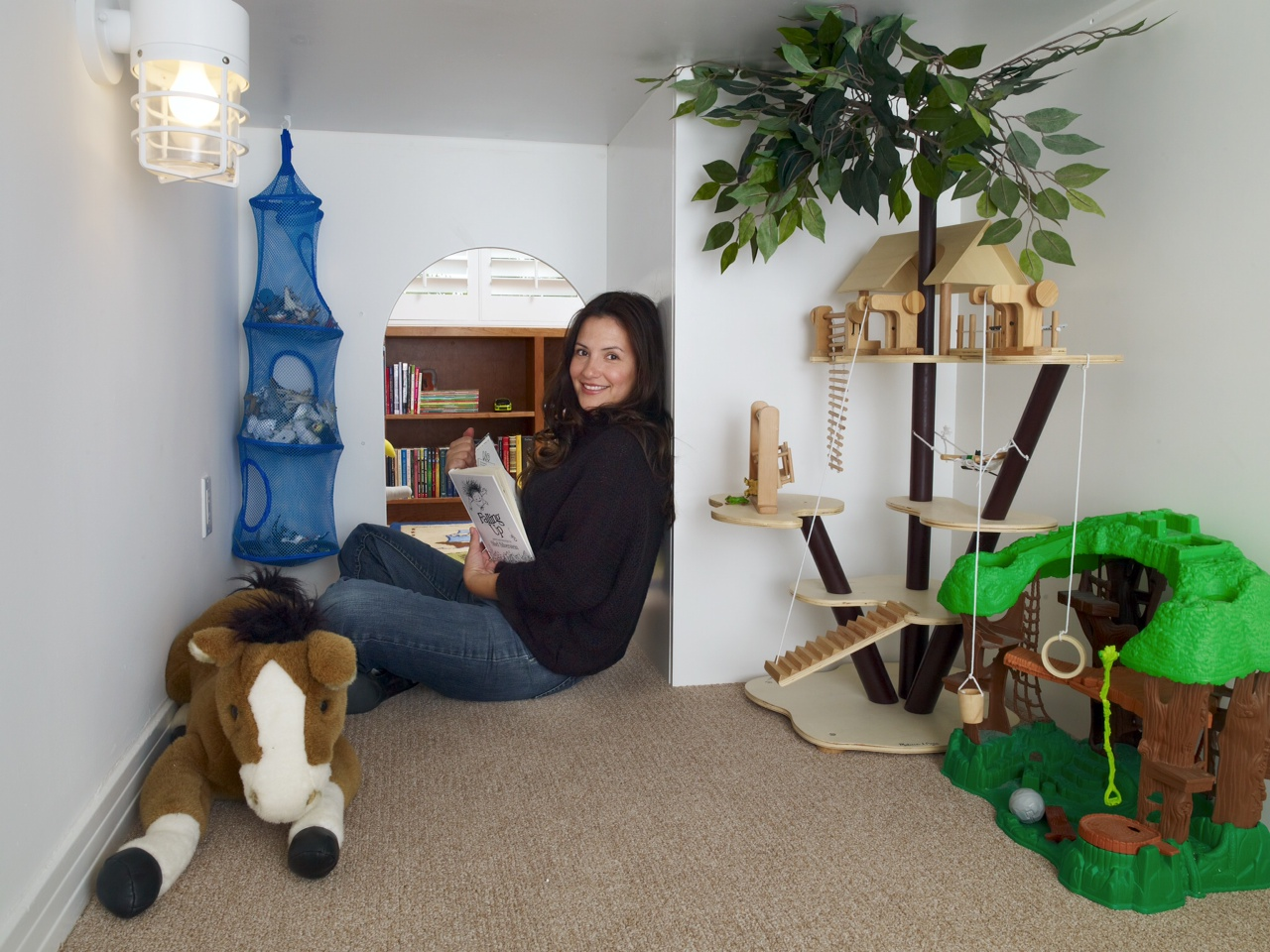 Designer Erica Islas grabs a book inside the lower space of the Palisades Kids' Room, showing it's big enough for adults as it is for children.