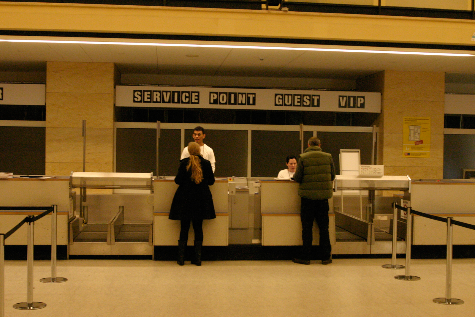 Visitors check in at the old airport check-in stands.