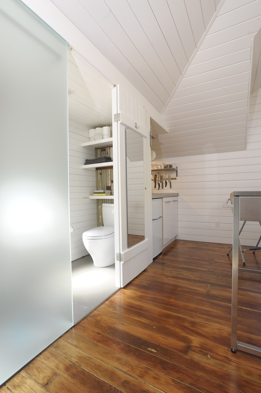 Azevedo shoehorned a small bathroom next to the kitchen, under the dormer. The etched translucent glass lets light into the main living area and serves as one side of the shower. Photo by Susanne Friedrich.
