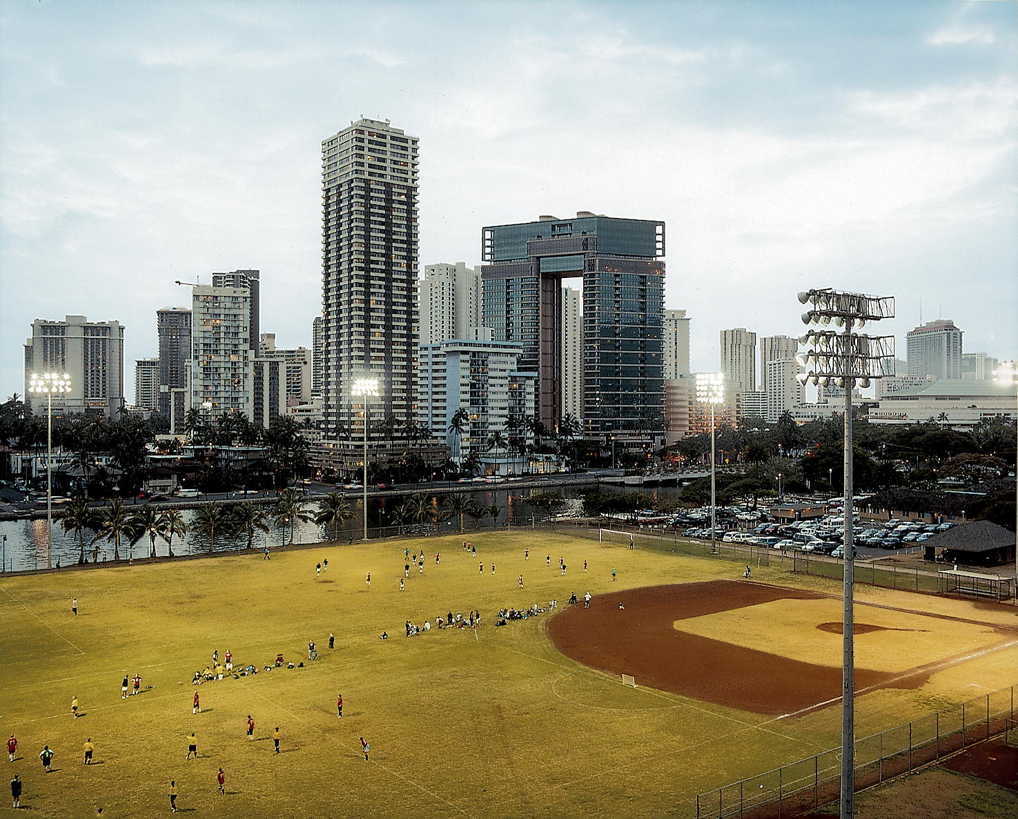 In the shadow of Waikiki's high-rises, a twilight soccer game unfolds at the Ala Wai Neighborhood Park. The now-polluted Ala Wai Canal was created in the 1920s to drain the swampland that would become Waikiki.