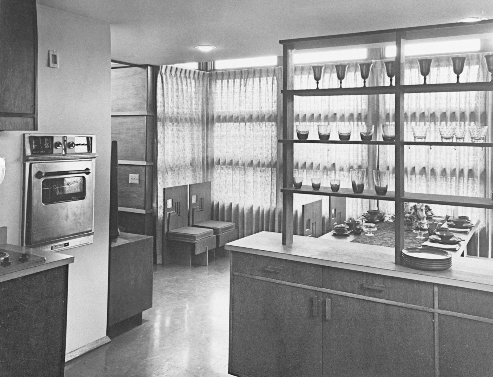 Interior of a prefab house showing kitchen looking out into dining room, designed by Frank Lloyd Wright.