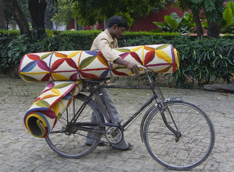 Not sure how he's going to ride his bicycle with two rolled-up Kala rugs, but....