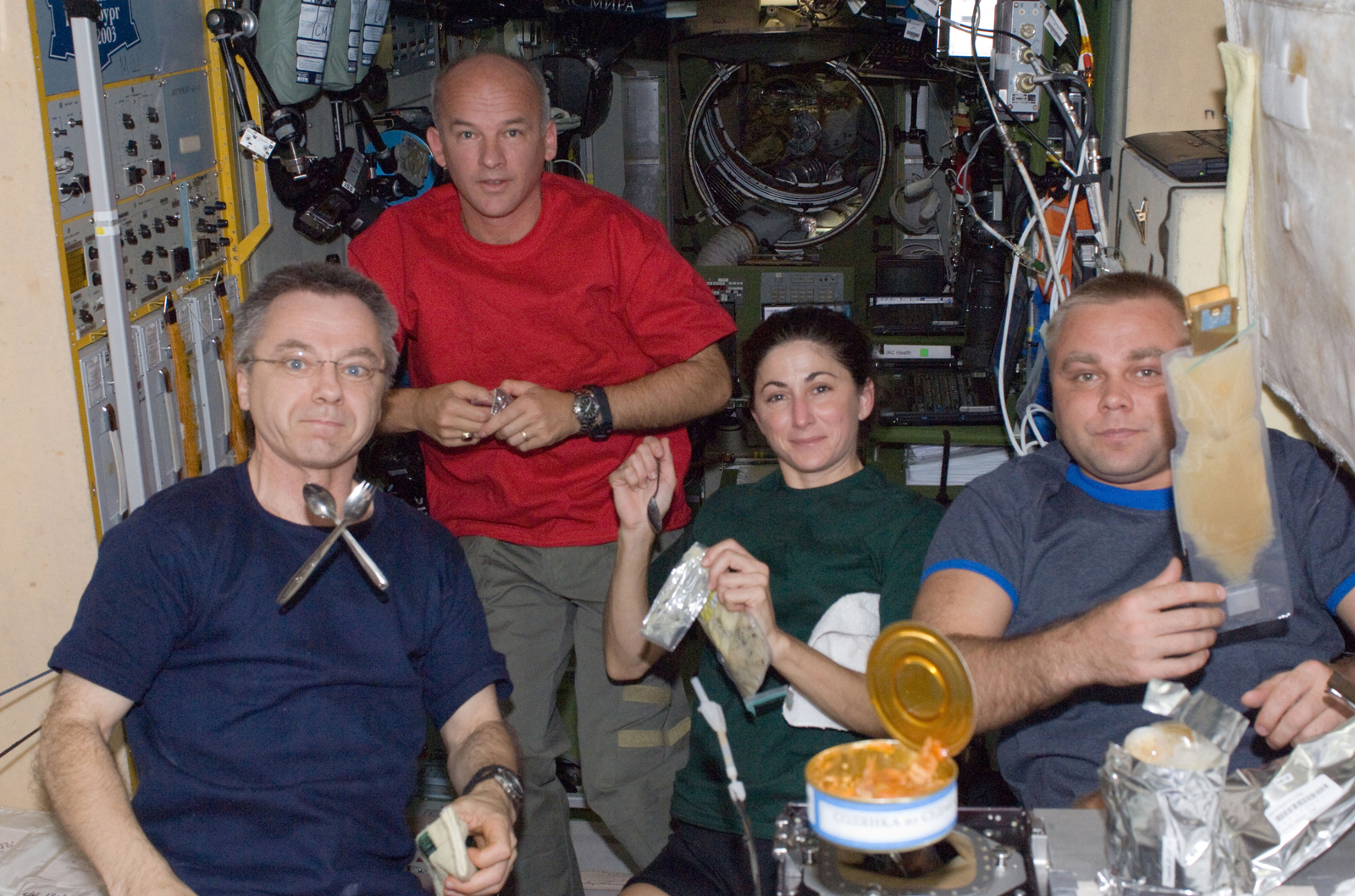 Canadian Space Agency astronaut Robert Thirsk (left), NASA astronauts Jeffrey Williams and Nicole Stott; along with Russian cosmonaut Maxim Suraev, all Expedition 21 flight engineers, share a meal at the galley in the Zvezda Service Module of the ISS. Pho