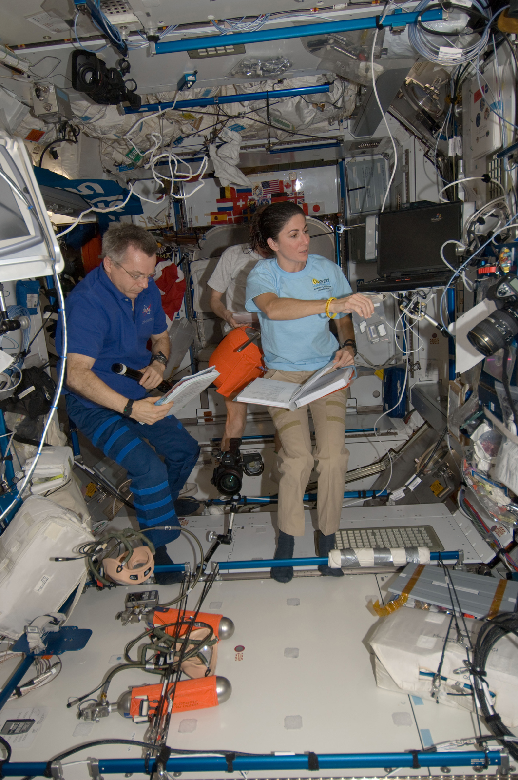 Canadian Space Agency astronaut Robert Thirsk and NASA astronaut Nicole Stott, both Expedition 21 flight engineers; along with European Space Agency astronaut Frank De Winne (background), commander, work in the Harmony node of the ISS. Photo taken October