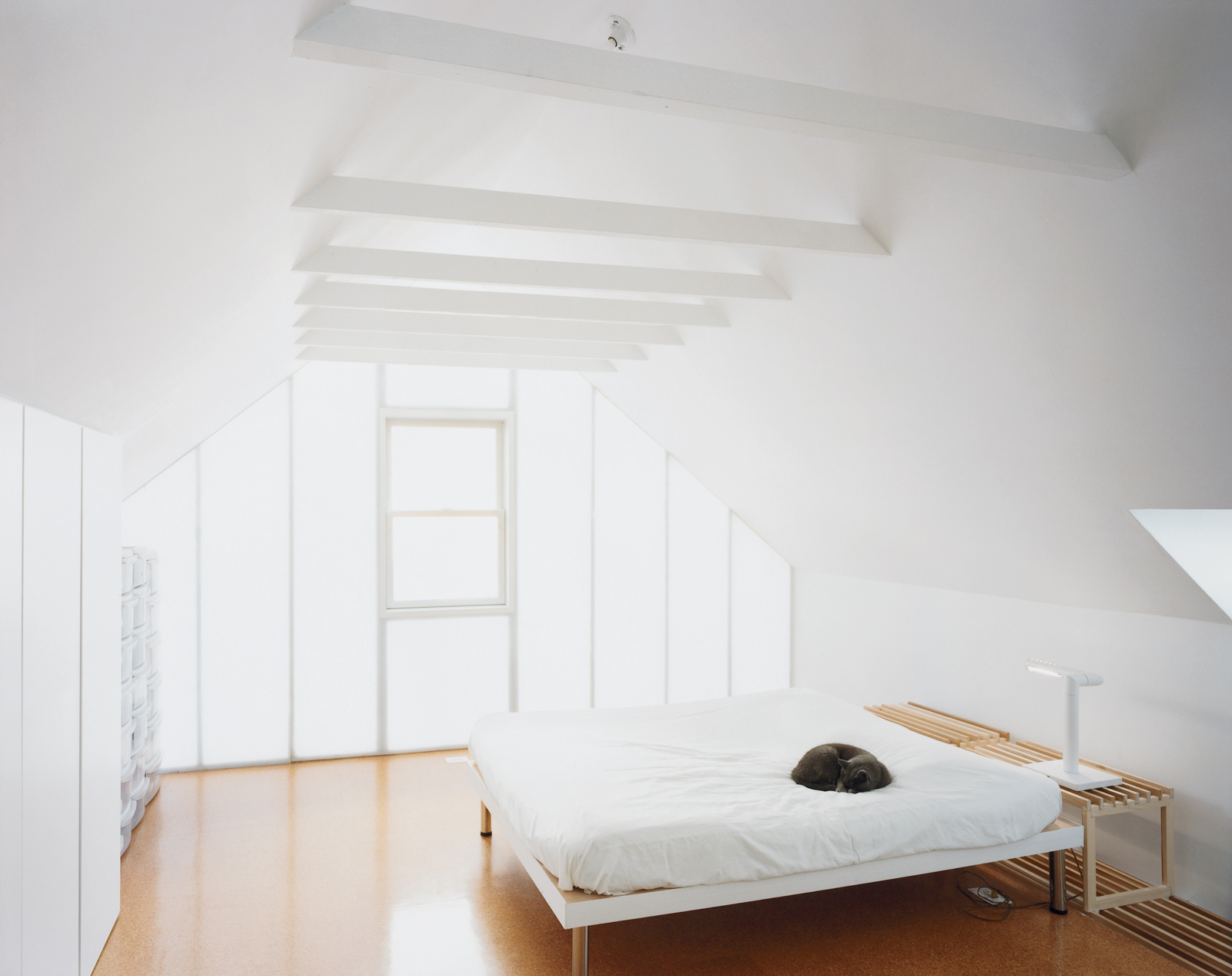 Uni exposed the ceiling beams, formerly concealed by drywall and a kitschy light fixture upon which Schenk would hit his head. They built a platform bed using a couple of hollow doors as a surface for the mattress.