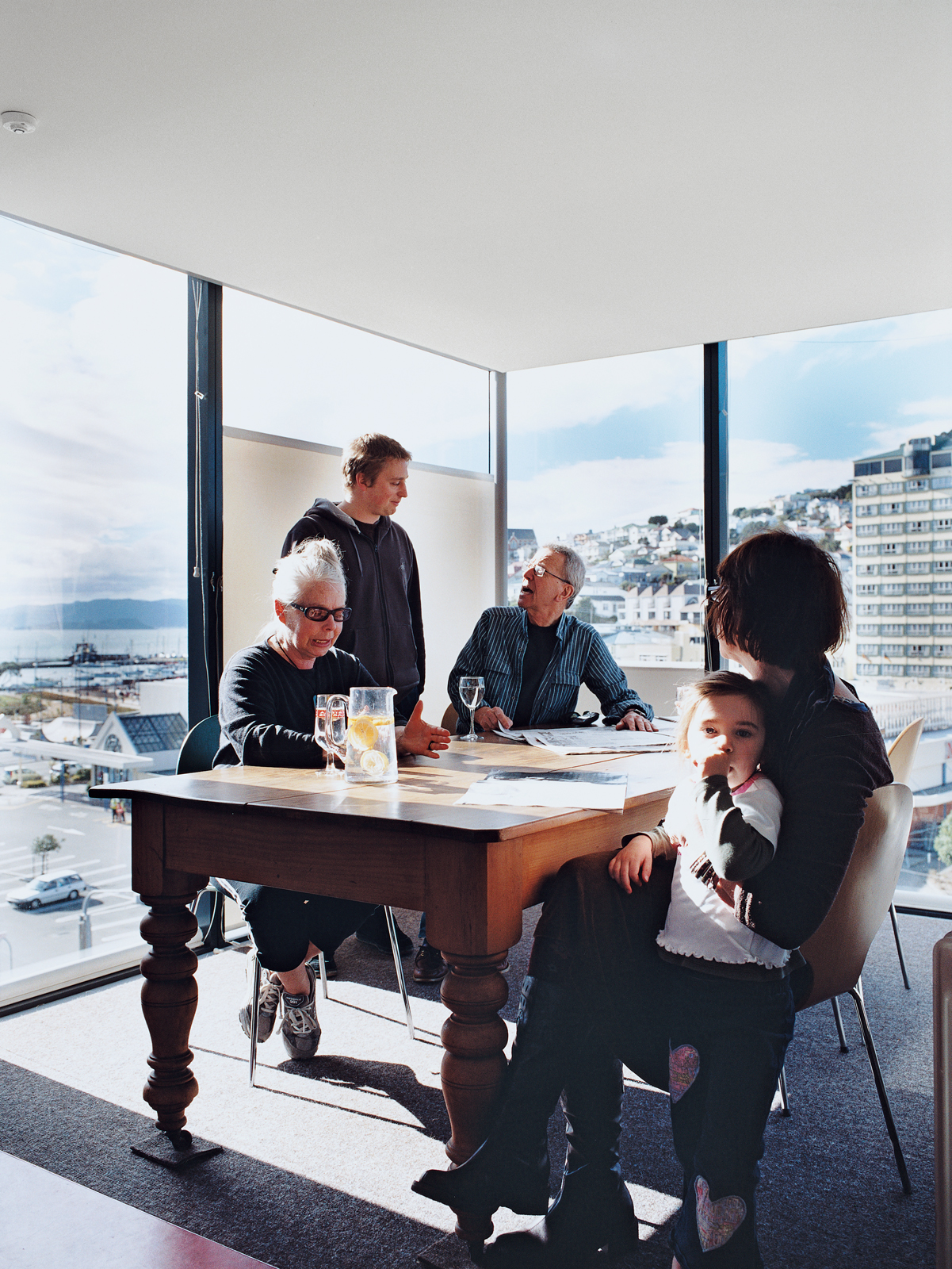 Jan Bieringa (seated, left) hangs out with her son, Kris Bieringa (standing), Tony Hiles, Judith Fyfe, and Fyfe's granddaughter, Phoebe Pottinger. Surrounded on three sides by glass walls, the dining room is the perfect spot to soak up the stunning views