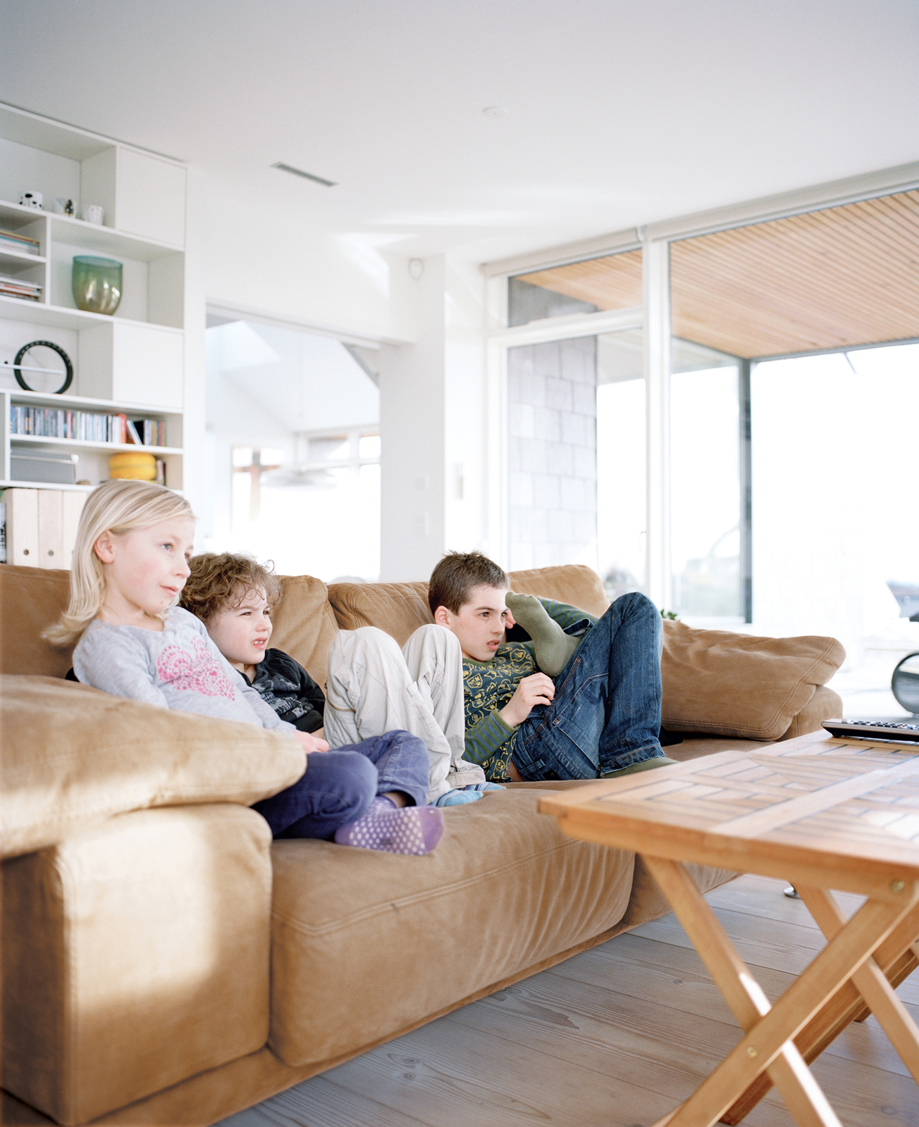 Axel, Anna, and a friend watch television in the living room.