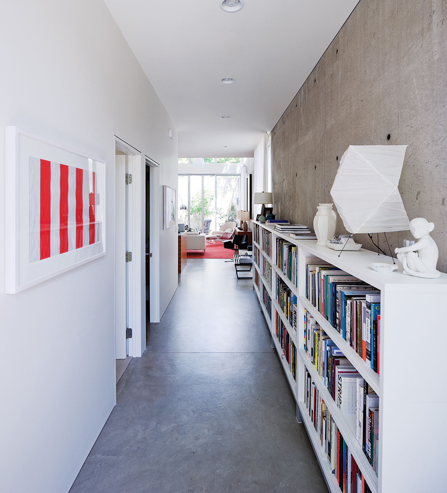 A portion of Blauvelt's 3,000-book library is archived in the long entry hall where the geometry of a Noguchi lamp plays off a pair of minimalist prints by Daniel Buren.