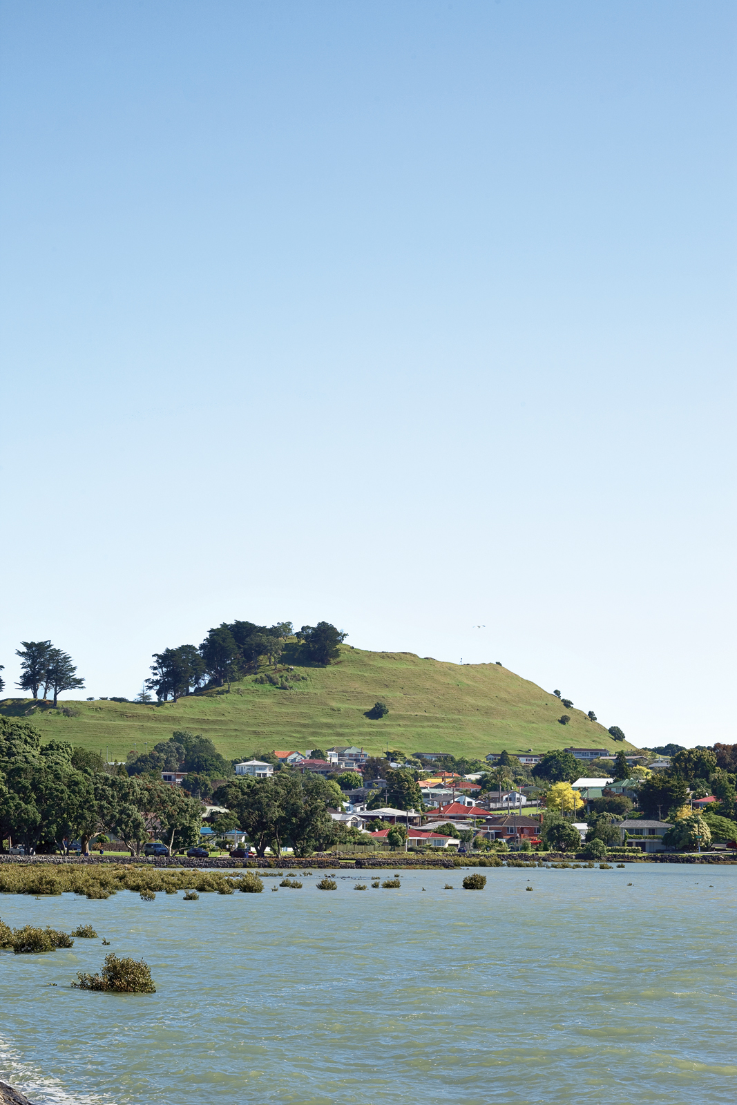 Auckland's Mangere Mountain is a dormant volcano that rises above the shore of the Manukau Harbor. It was once a site of strategic importance to early Maori tribes, and development is now prohibited on its cone.