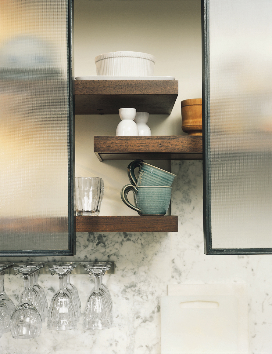 The Feld kitchen bridges eras by bringing together traditional designs and materials (the big Shaw's Original English farmhouse sink, fir floors, honed marble counters) with industrial designs. Open walnut shelving helps convey a sense of lightness. The p