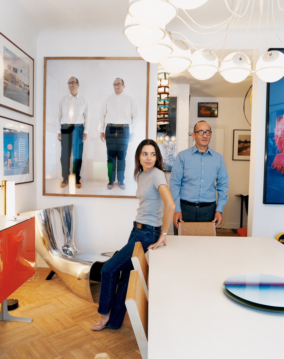Didier Krzentowski and his wife, Clémence, in the dining room of their Paris flat. The Slim table was designed by Martin Szekely for a Galerie Kreo exhibition in 1999. On the wall, above a Marc Newson Alufelt chair, is a photograph of Krzentowski by Erwin