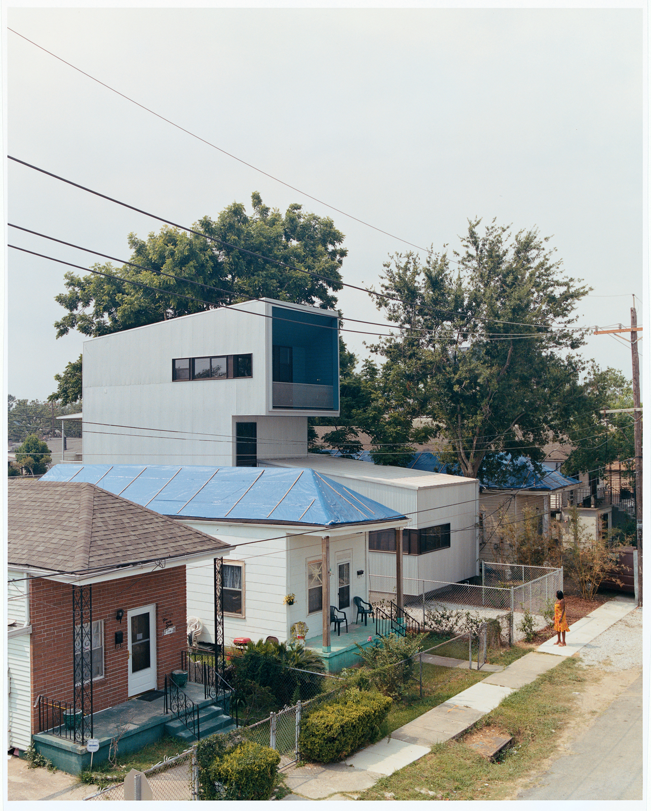 Bild Design introduced the new structure seamlessly with the help of builders A.J. Christiana Construction. Ms. Doris, whose tarp-clad house to the left lost much of its roof when Hurricane Katrina struck, checks out her new neighbor.