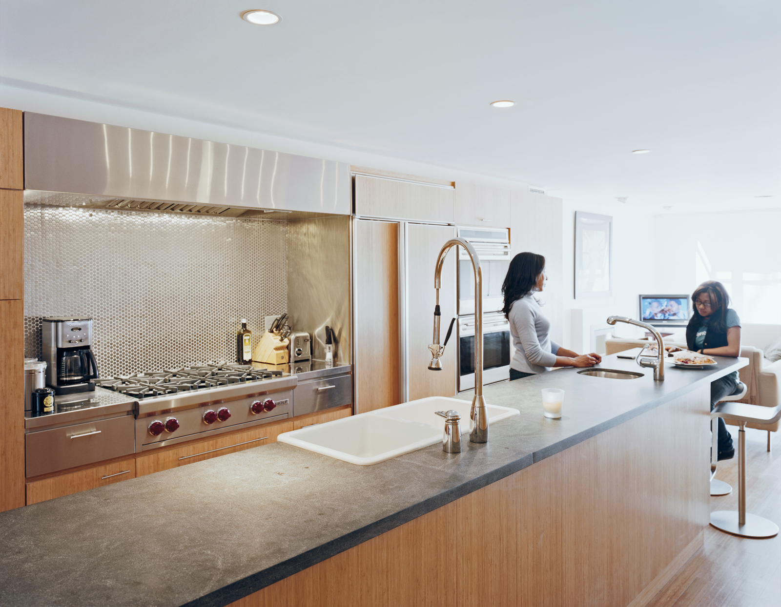 The kitchen has ample cooking space and room for a crowd. The Ann Sacks tile backsplash softens the line of the stainless steel, while the black absolute granite countertop adds a muted counterpoint. Kohler and Grohe fixtures ensure that dishes can be tac
