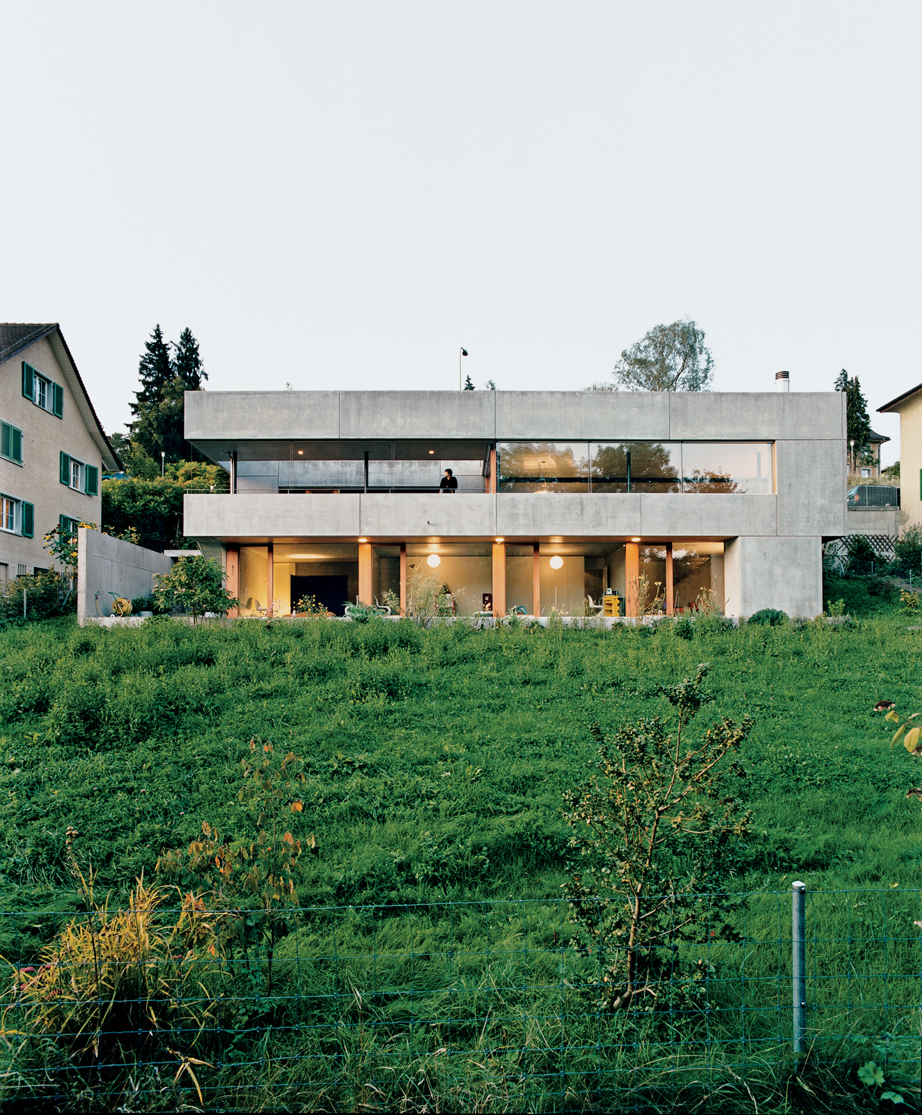 The rear of the house looks onto a lush backyard. The rough, industrial prefabricated concrete panels by the German manufacturer Syspro are the building blocks of the home.