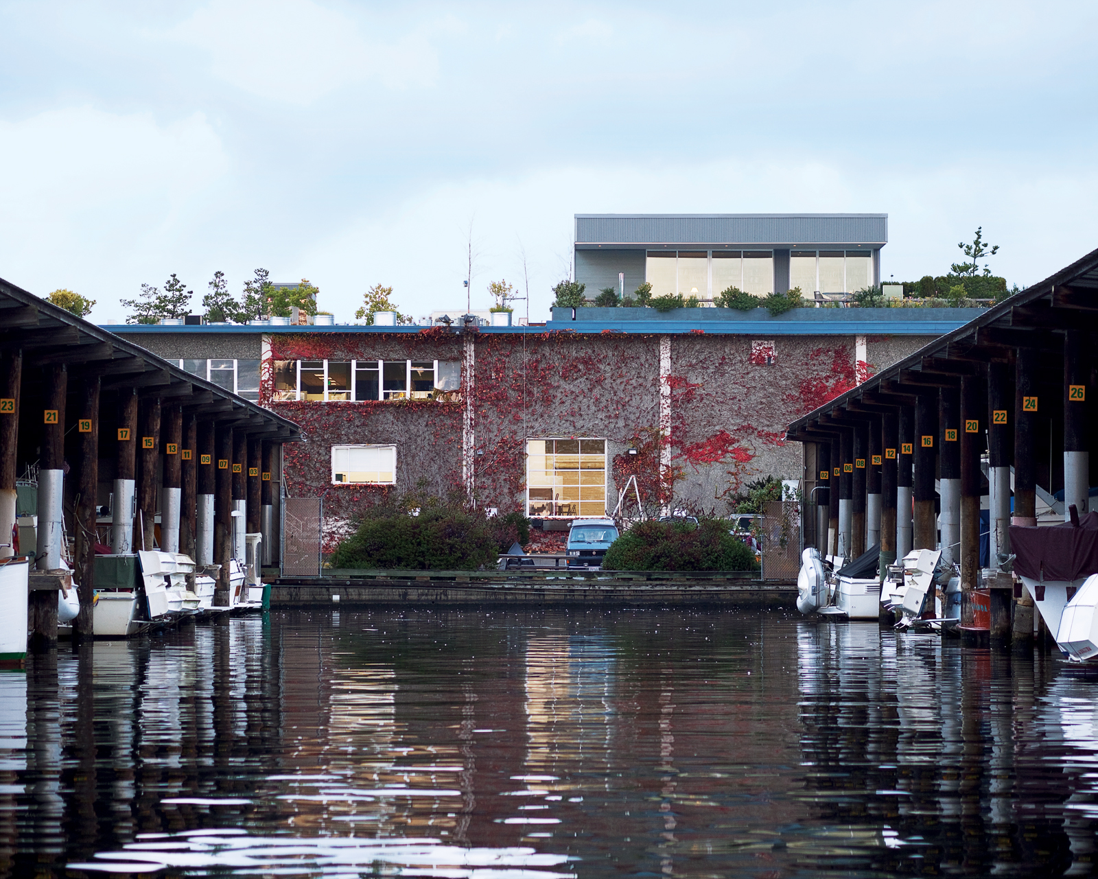 Atop a warehouse/office building overlooking Seattle's Salmon Bay waterway, Tom Bayley's home watches over a 250-slip marina. Few tenants below notice his presence, except when errant drops from his watering can fall from his deck, 25 feet above.