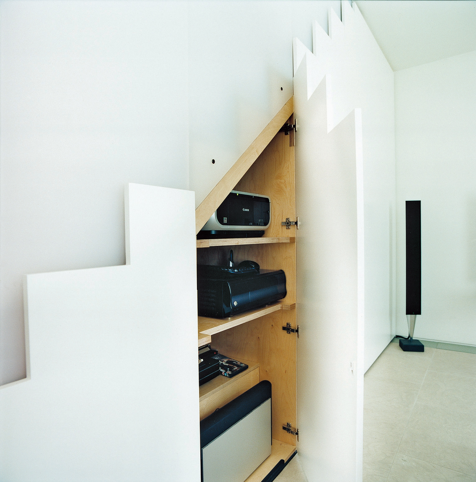"In keeping with the maxim ""a place for everything and everything in its place,""  any A/V equipment that does not need to be on show is hidden away in these neat push-to-open cupboards beneath the stairs. This means that you'd never spy  an unsightly trail"