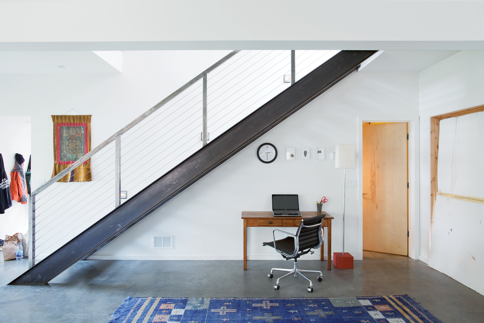 Small work table by stairs and blue patterned rug
