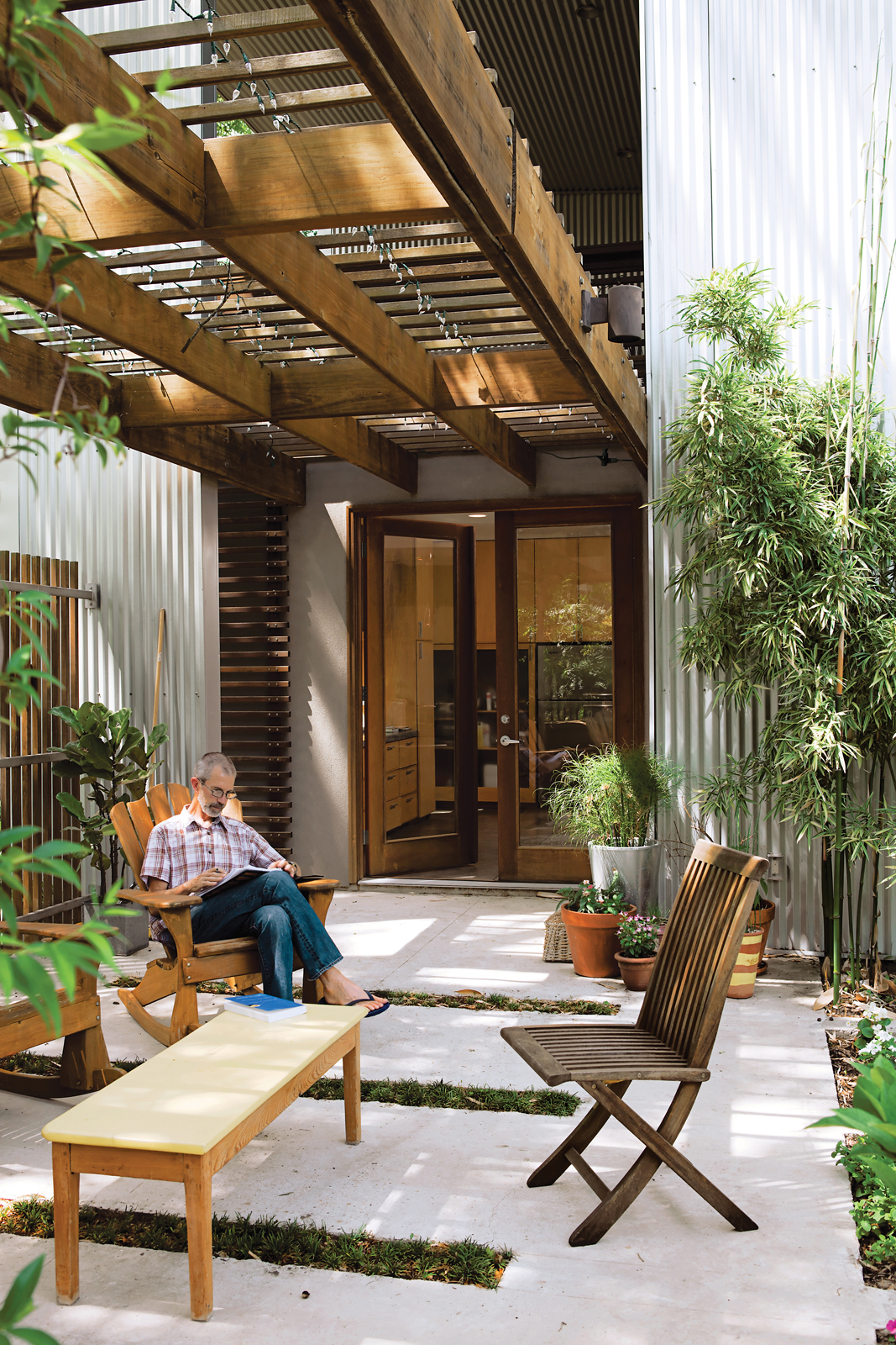 Catovic Hughes's design for the Morelands is all about embracing the outdoors. Rick spends as much time on the patio as he can. The undulation of the aluminum cladding makes a regular, rhythmic backdrop for the yards-high bamboo he lovingly tends.