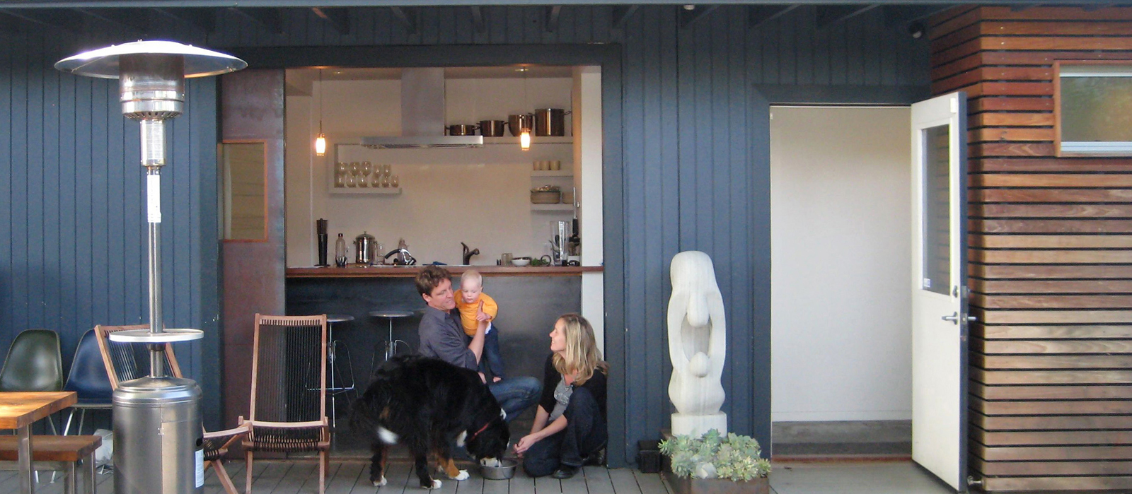 "Shoup, his wife, Taya, and daughter, Hannah, relax on the deck off the kitchen with their dog, Stella. ""For a high percentage of the year, we just roll open the door, and everybody hangs out in the kitchen, where we can keep an eye on Hannah,"" explains Sh"
