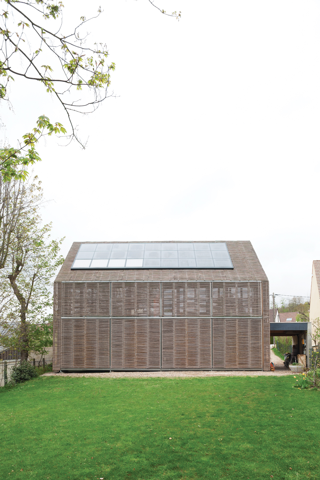 Modern bamboo-clad farmhouse with solar panels
