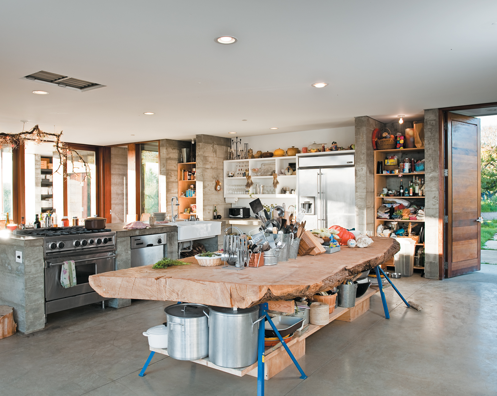 A massive slab of cypress perched atop sawhorses provides storage for pots and utensils.