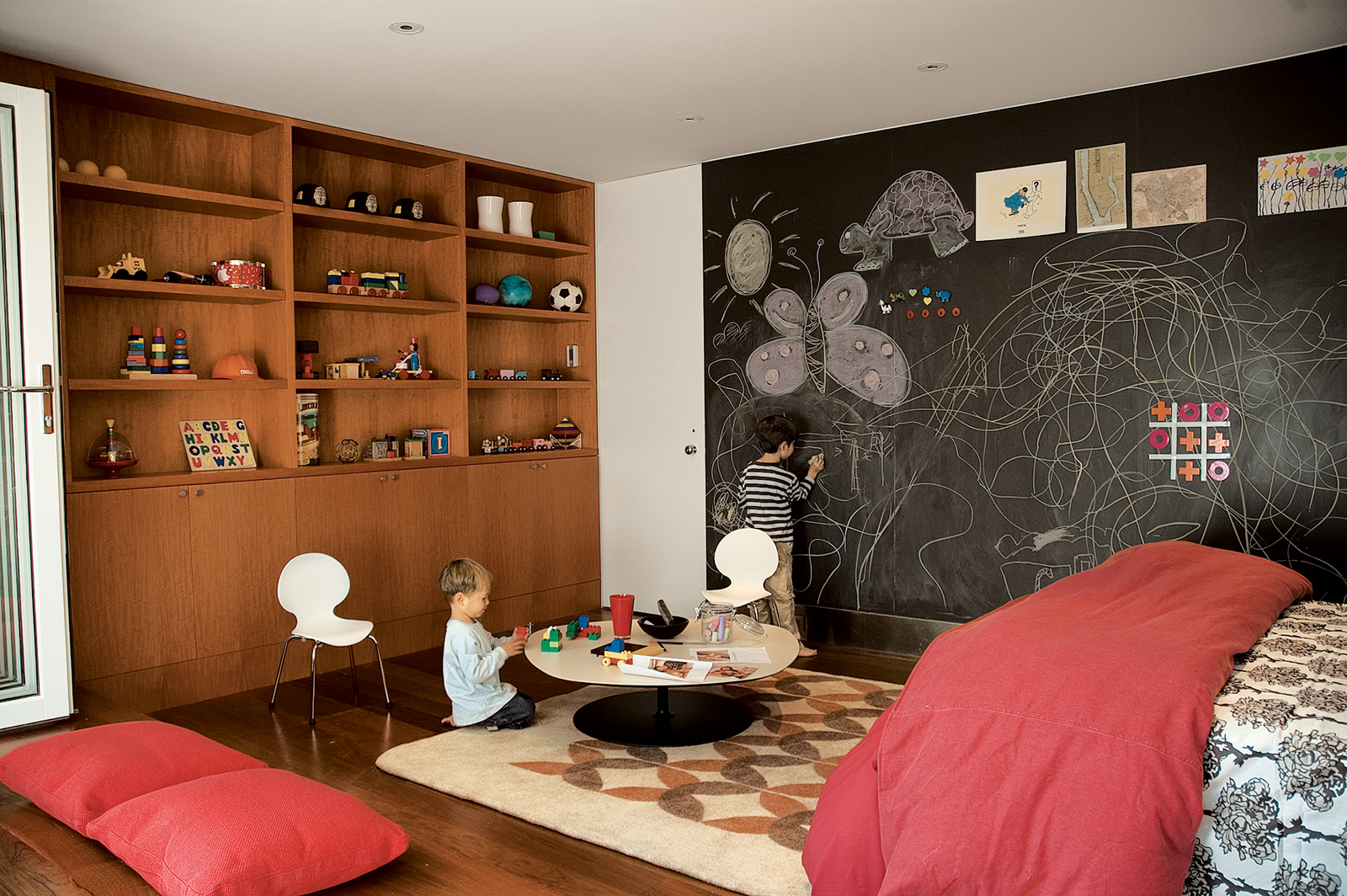 Inside a renovated garage in San Francisco, writing on the walls is encouraged by the magnetic slate chalkboard from Claridge Products. The Phoenix table by Patricia Urquiola for Moroso does double duty as a play table or a coffee table, depending upon wh