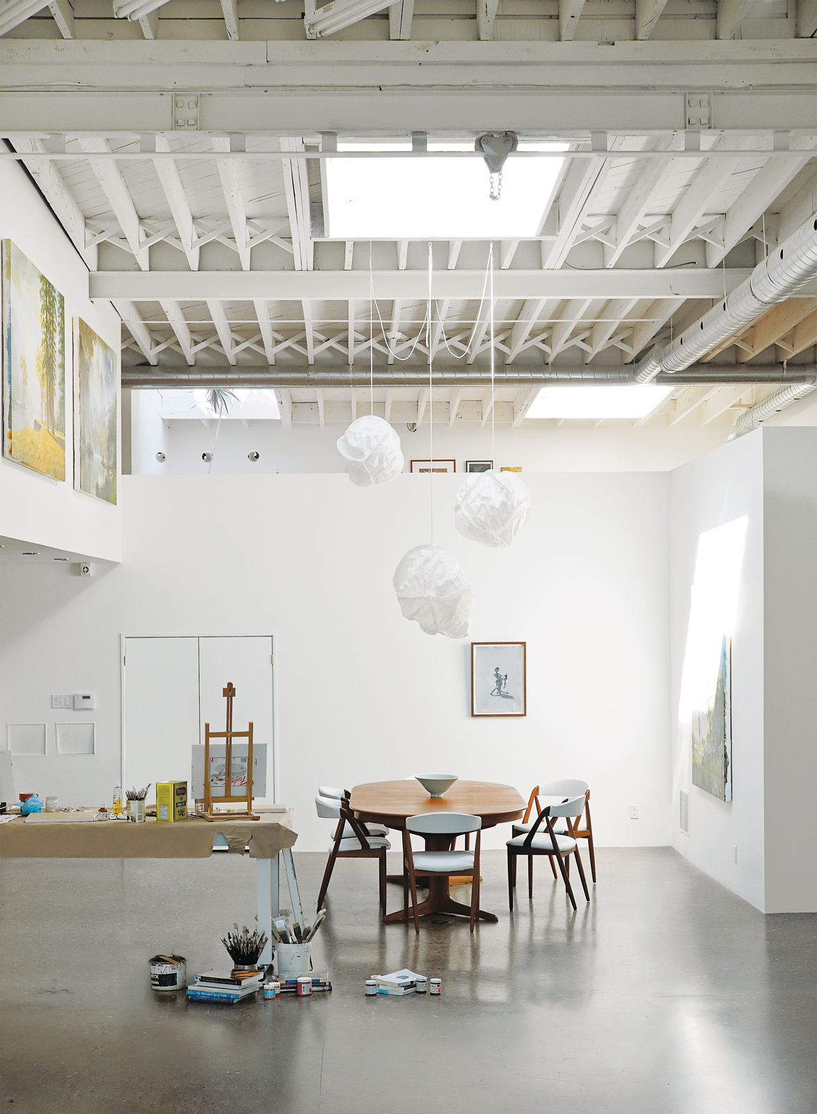 Dining area with vintage Danish dining set and Cloud pendants by Frank Gehry