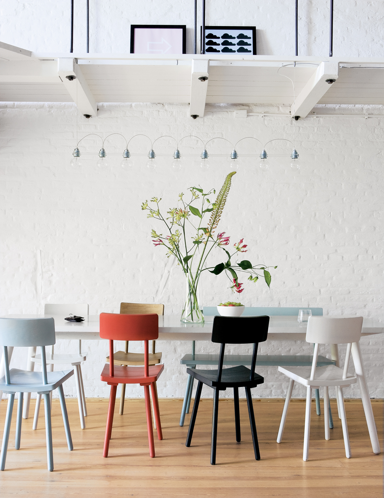 """Piet Hein Eek's wooden chairs add a touch of color to the monochromatic apartment. """"I'm a fan of simple modern furniture, with a twist,"""" says Carr. """"I wanted to buy everything from Piet Hein Eek."""""""