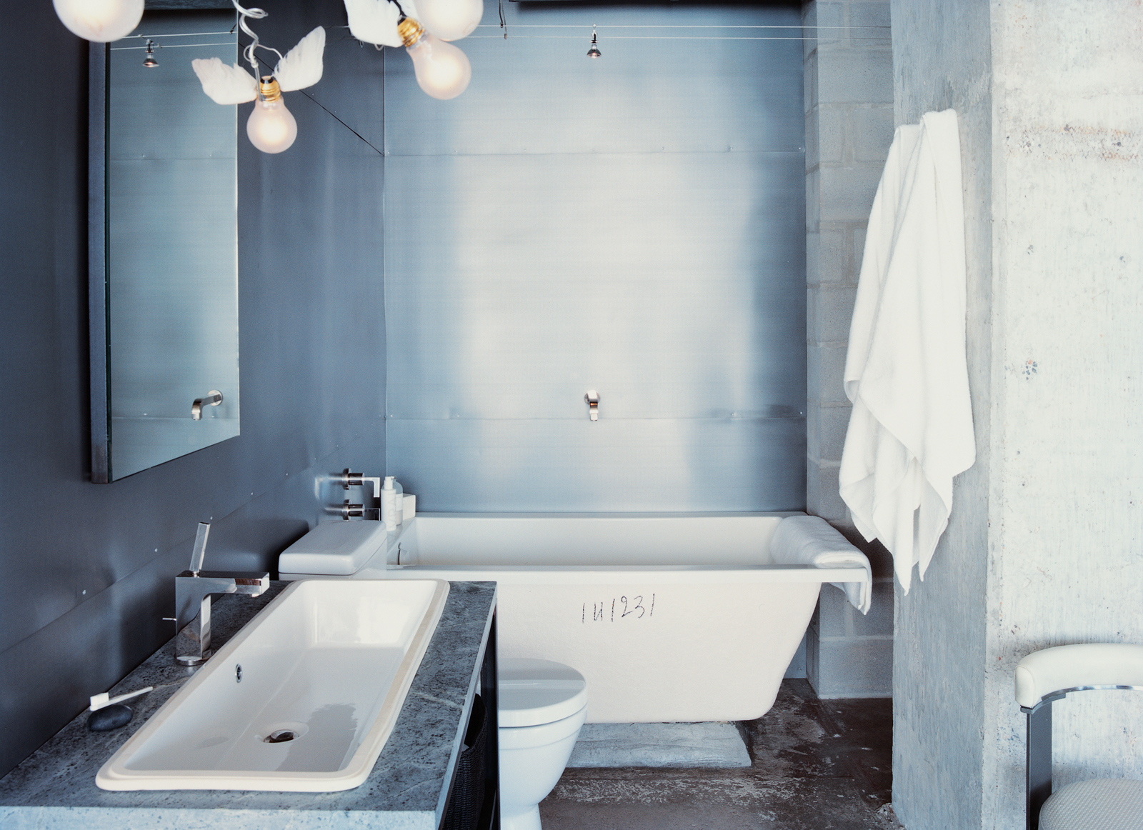 Winged light bulbs, part of an Ingo Maurer fixture, bring levity to Hill's bathroom. The space features a zinc wall by Houston metalworker George Sacaris, who also did the bathroom and kitchen cabinets,