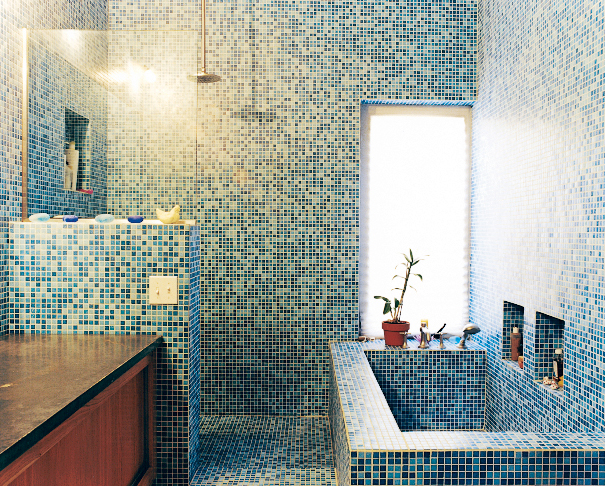 The blue-tiled master bathroom stands in contrast to the muted tones of the rest of the house. The tile is recycled glass from China.