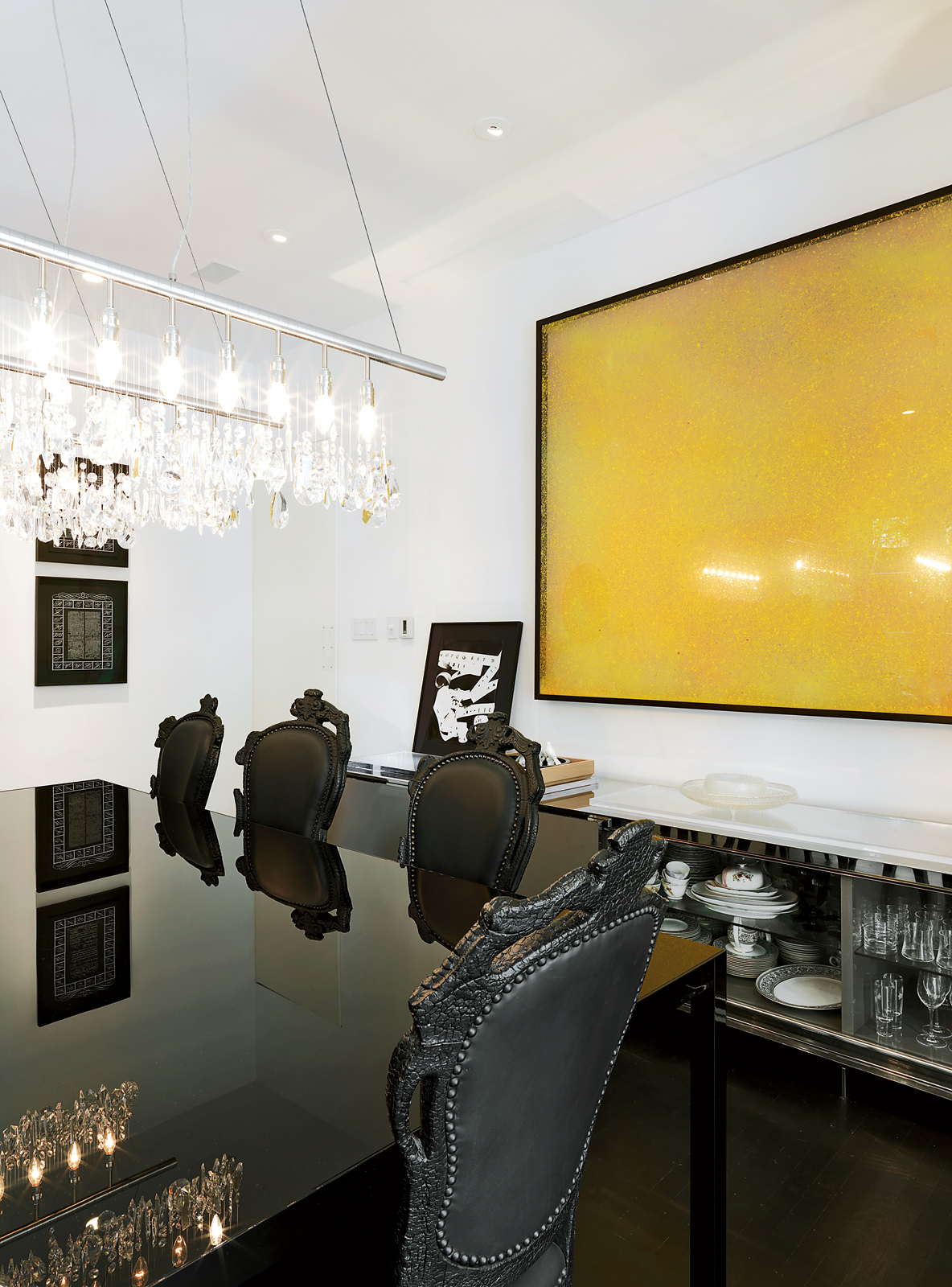 Modern dining room with black furniture and Cellula chandelier