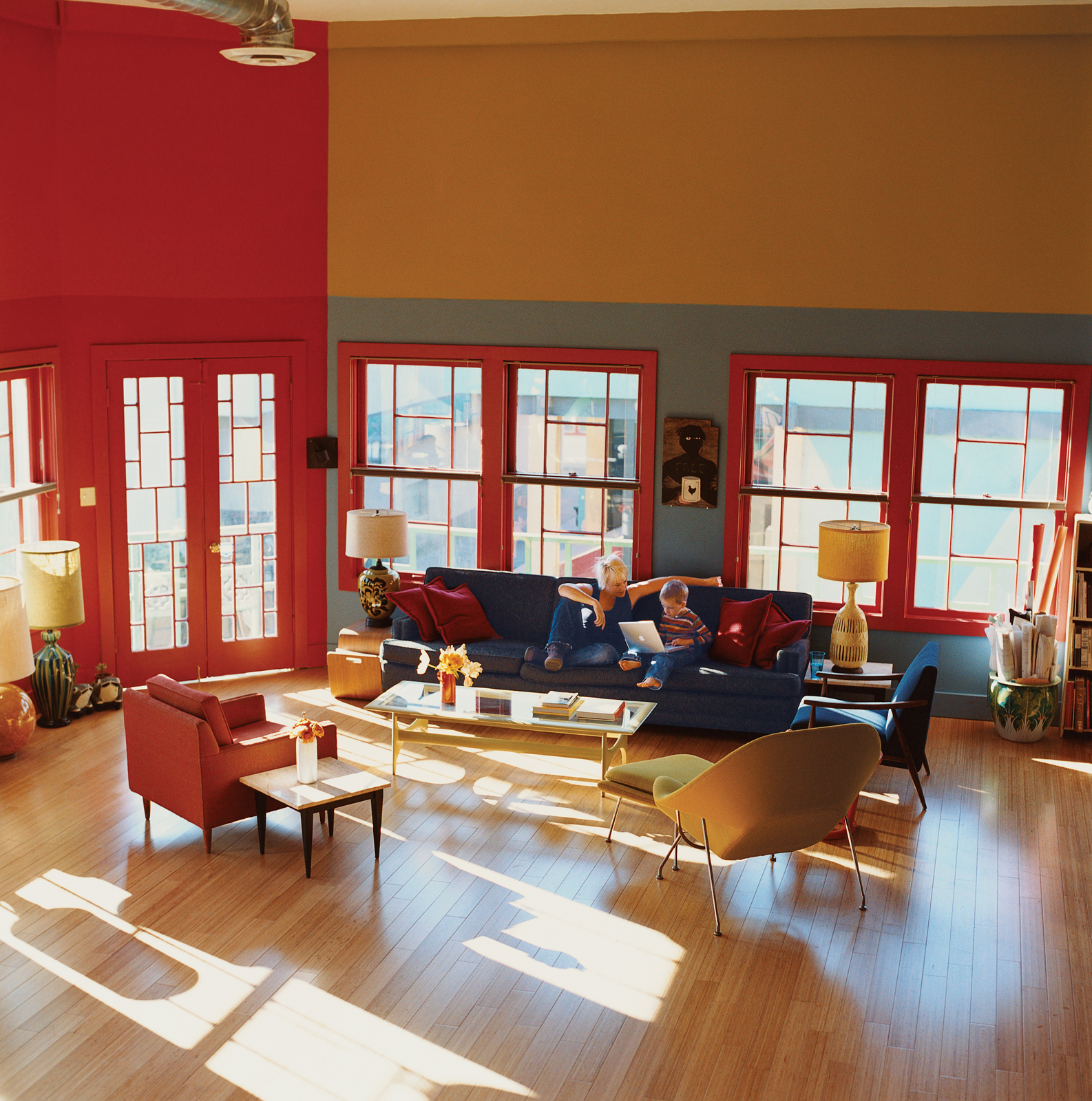 """Sunlight streams through formerly boarded-up windows in the living area that was once Madame Wong's stage. """"When we took off the drywall, we realized there were windows in there. So we had more made to match these four,"""" says Dan. The new windows open up"""