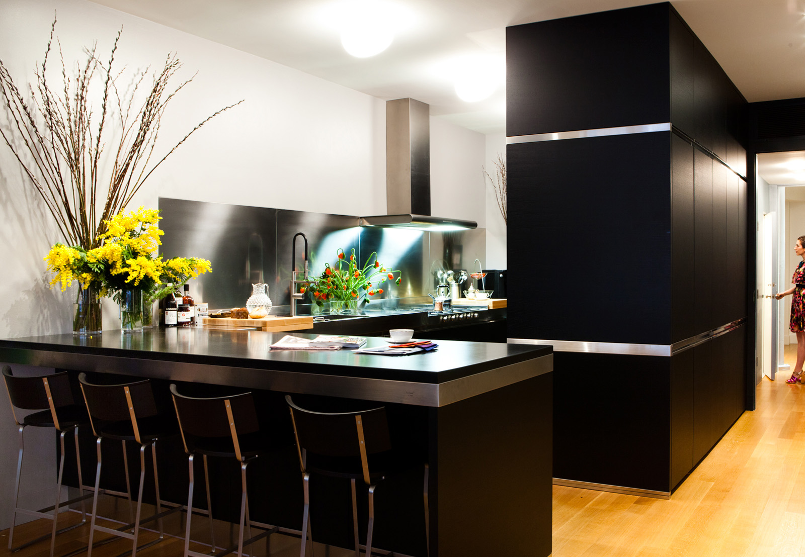 modern kitchen with stainless steel finishes, black cabinetry, and granite countertops