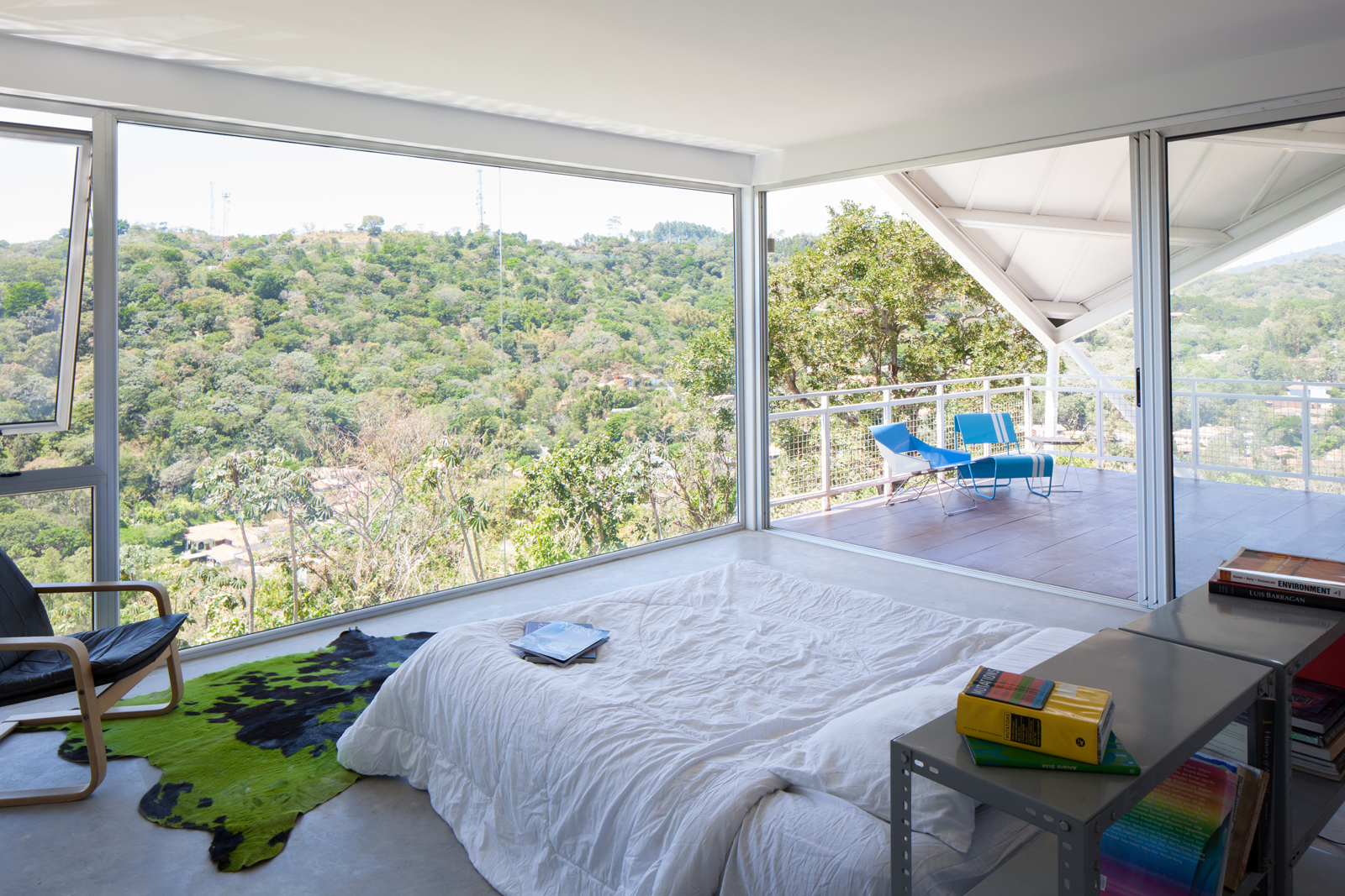 master bedroom with floor-to-ceiling glass walls in a modern house in el salvador with creative roofing