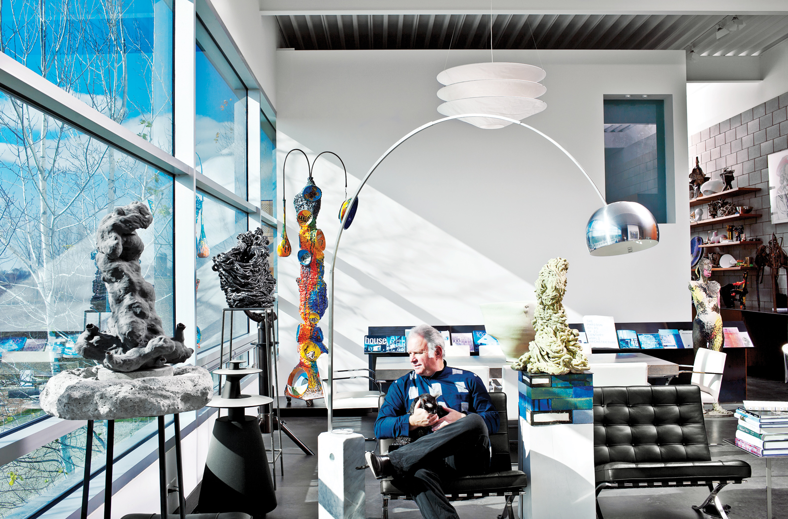 Resident in living room with sculptures and black furniture