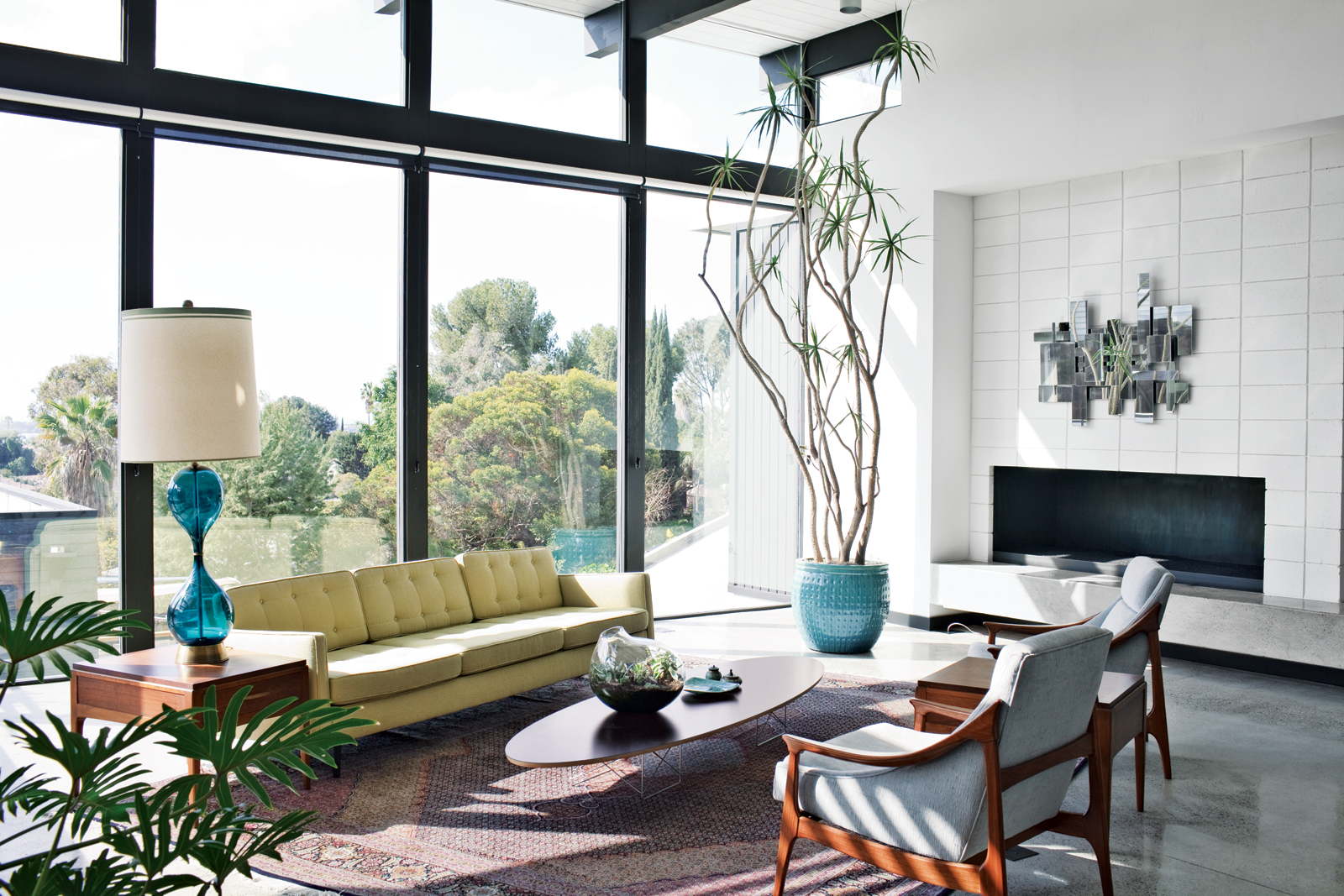 Yellow sofa, gray chairs, low coffee table, floor-to-ceiling windows