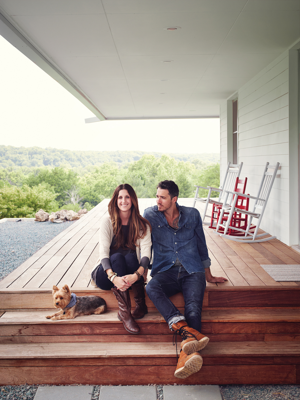 Young couple sitting on their wooden front porch with steps
