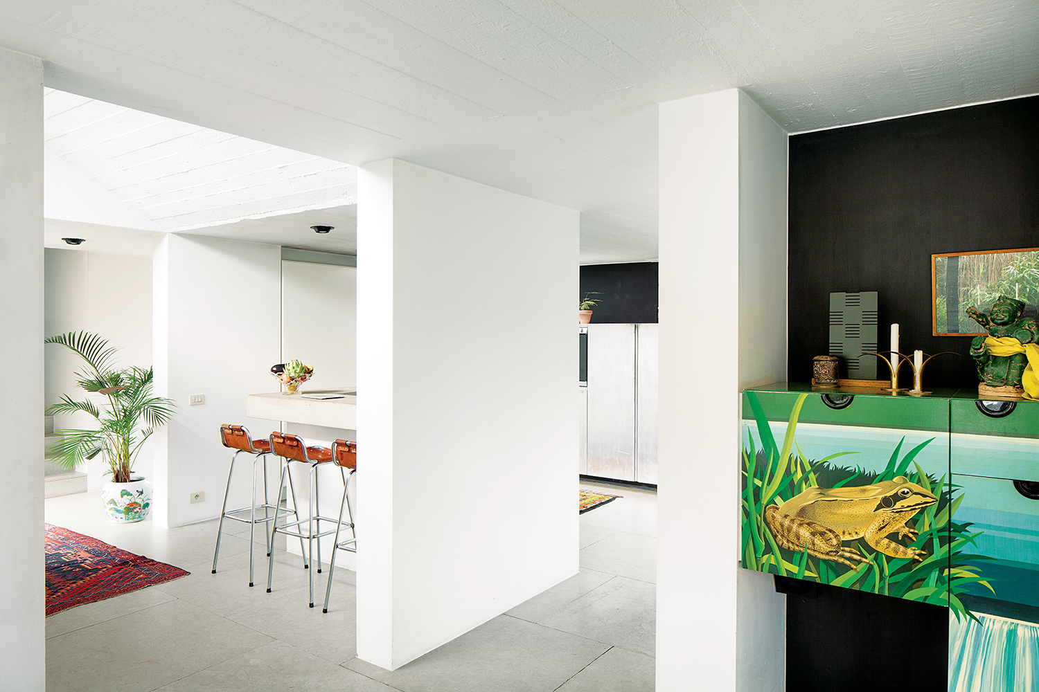 an original painted cupboard remains in the open black and white space of the renovated dining room