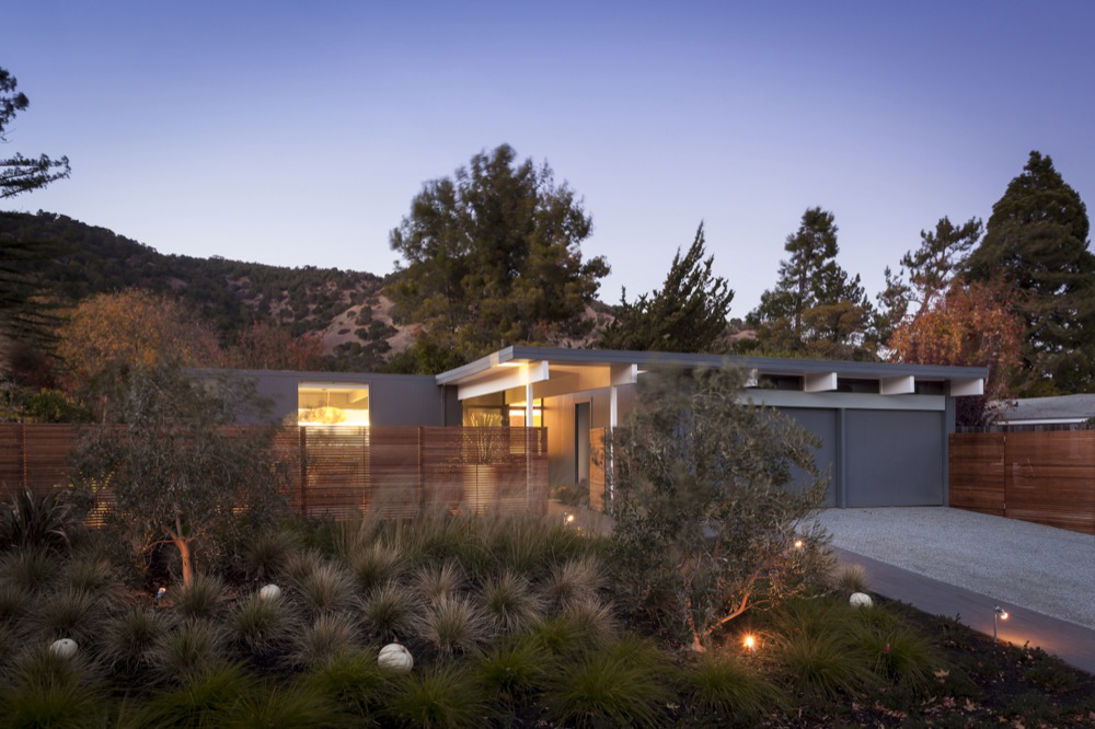 the exterior of a renovated Eichler home at night