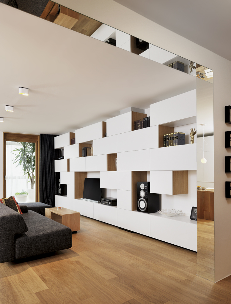 modern living room with built-in shelving and gray sofa and mirror