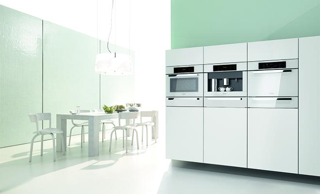 Pale green kitchen with modern appliances and table and chairs