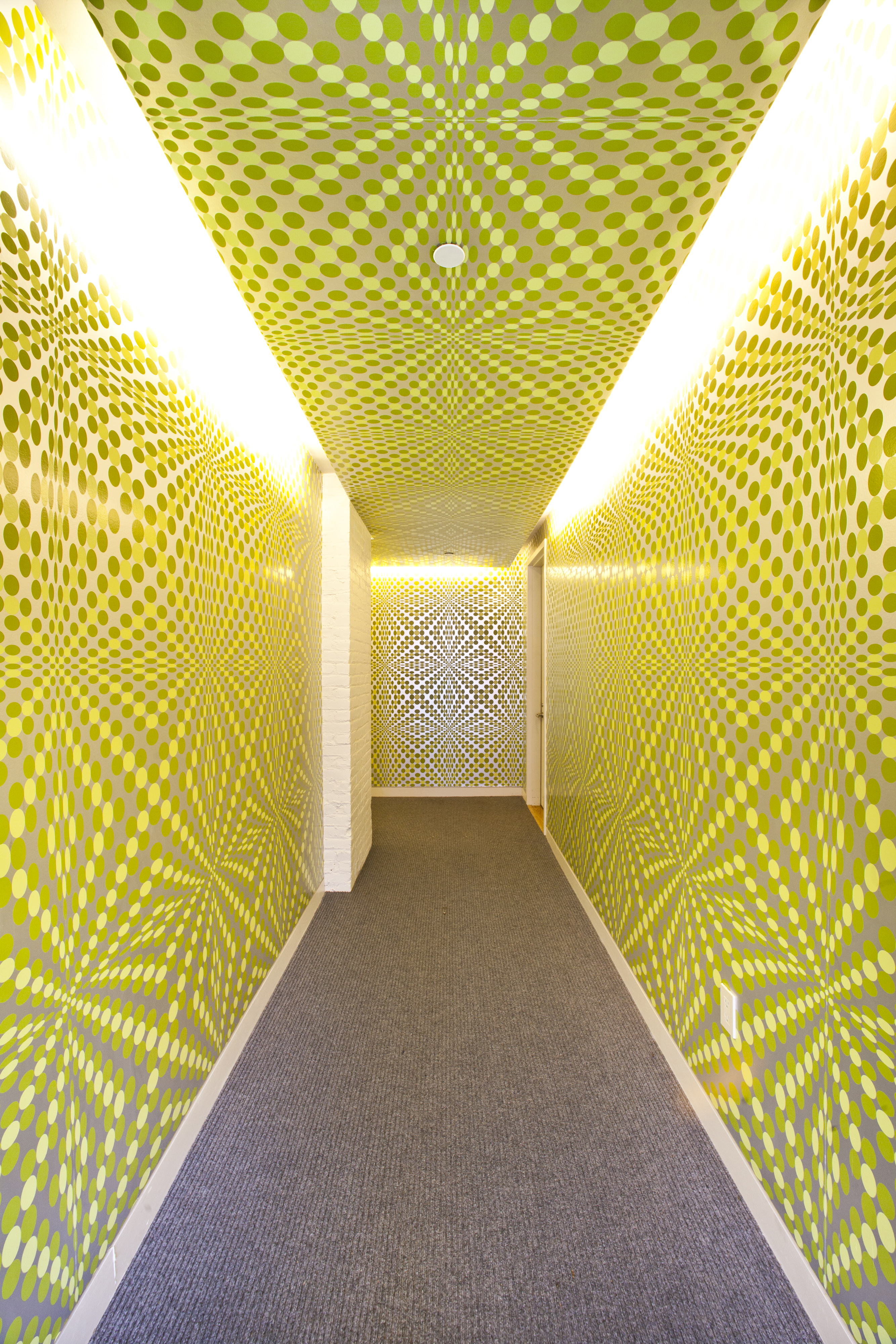 Graphic optical yellow wallpaper in a hallway