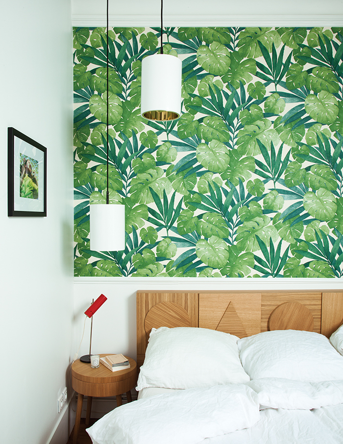 Wooden geometric headboard with green plants wallpaper
