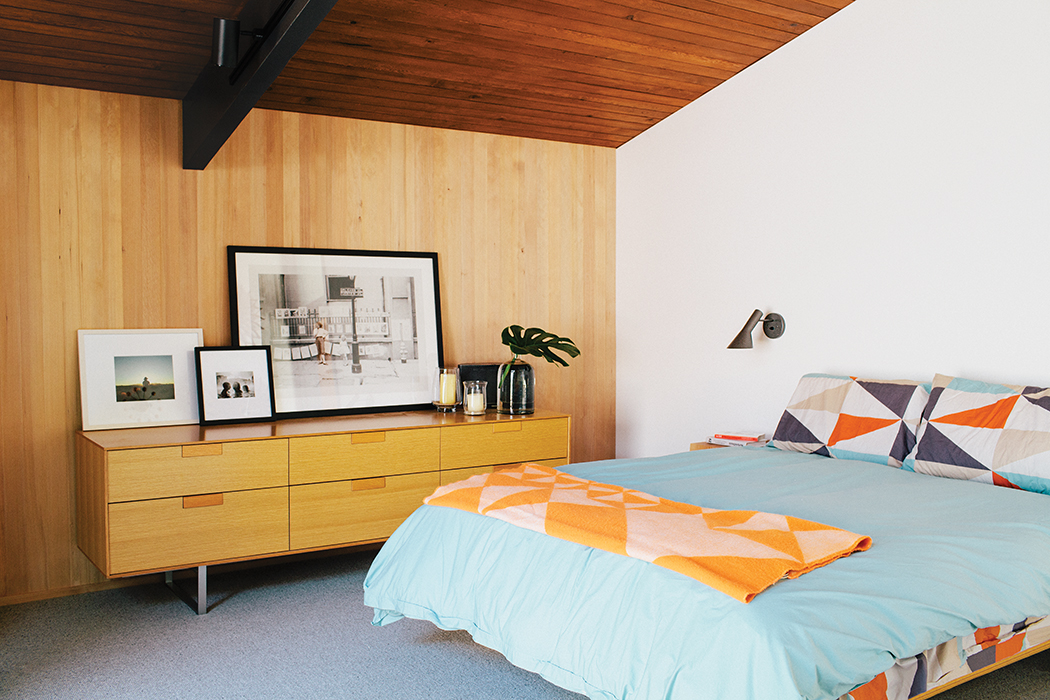 Midcentury Portland home master bedroom with Arne Jacbonsen sconces and Blu Dot bed and console