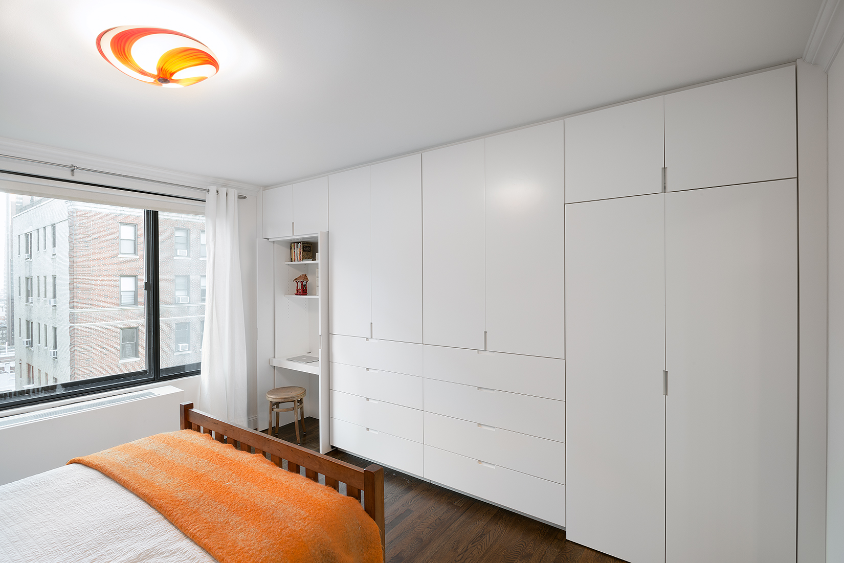 Upper East Side master bedroom with custom storage unit and desk
