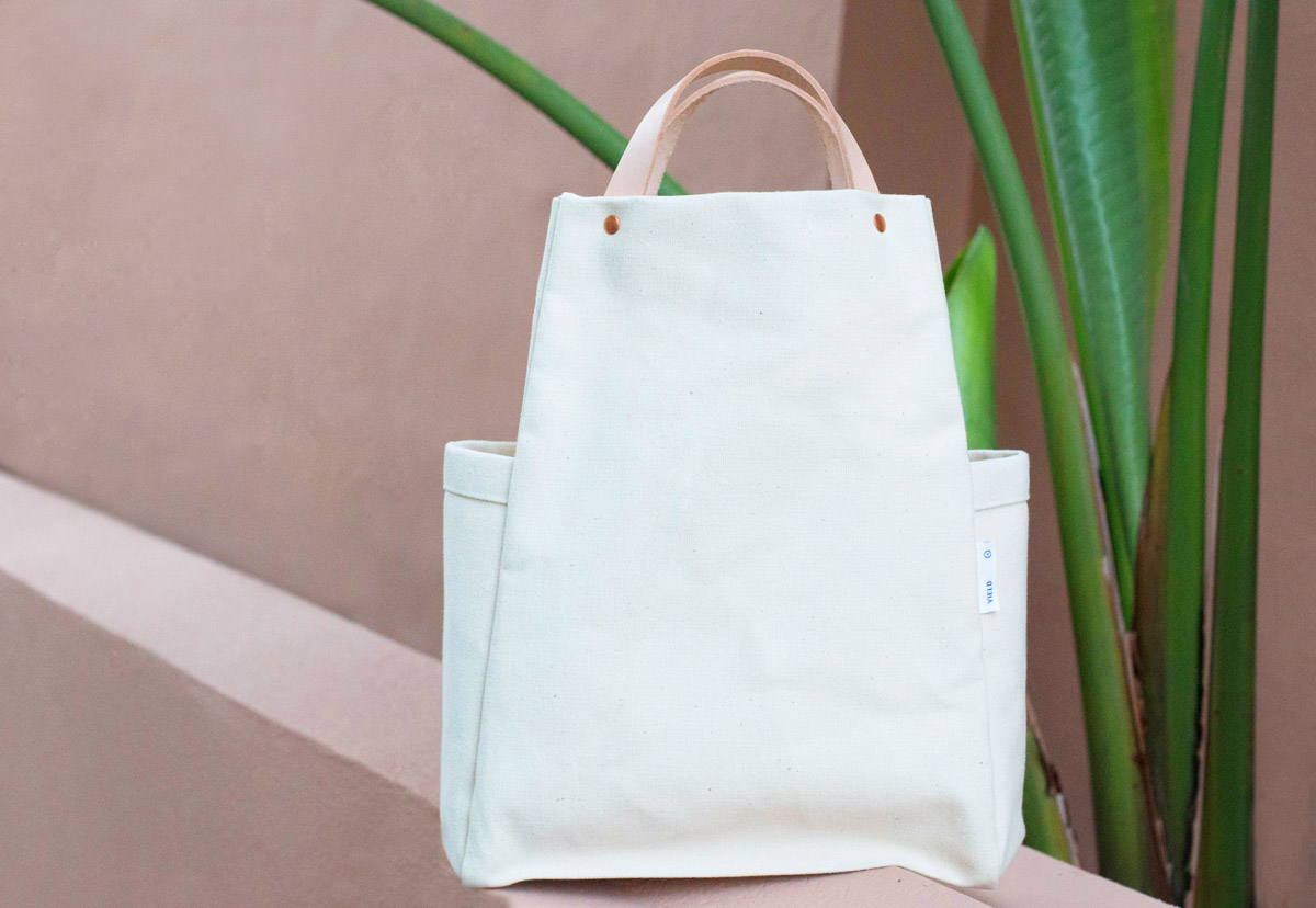Elegant and utilitarian canvas tote with copper rivets and vegetable-tanned leather handles