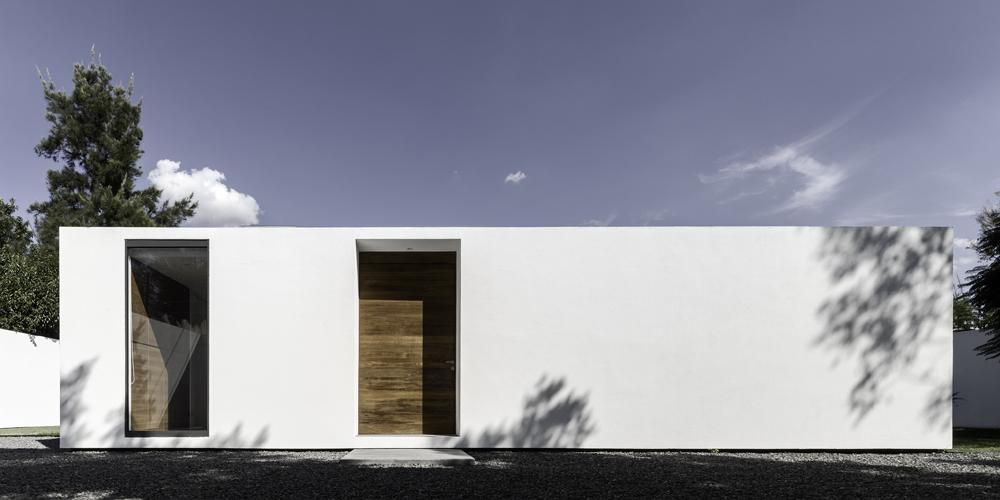 White facade for shadows of weekend home by Asociacion de Diseno in Mexico.