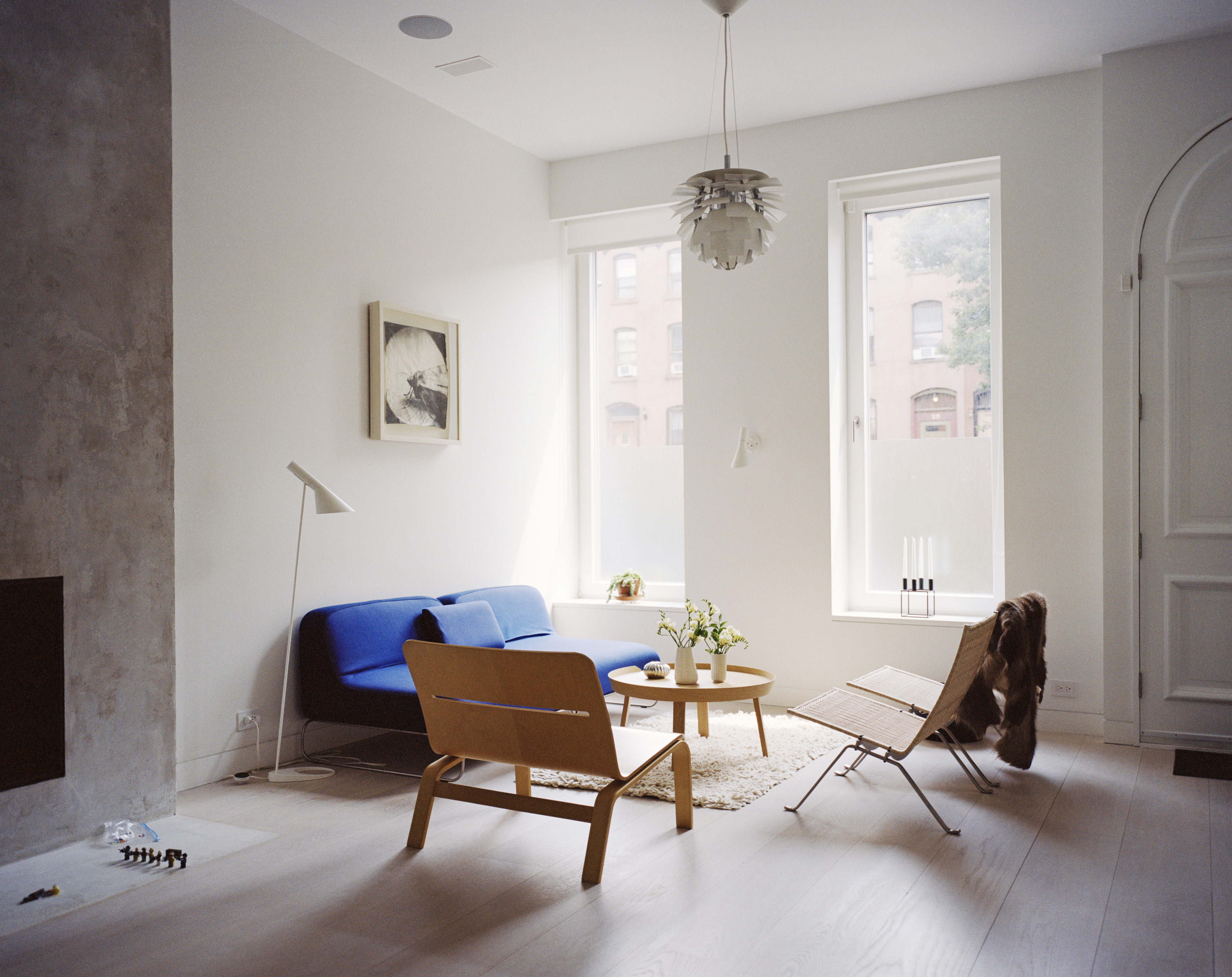 The living room is furnished with designs from Fritz Hansen, Muuto, Louis Poulsen, and Living Divani.
