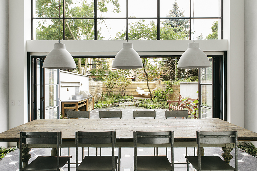 Dining room with sliding doors to garden in Brooklyn renovation by Elizabeth Roberts.