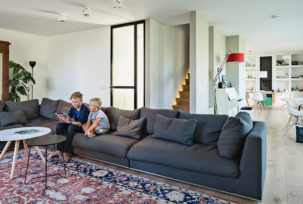 Amsterdam canal house living room with cocoon sofa, persian rug and illuminated stairway